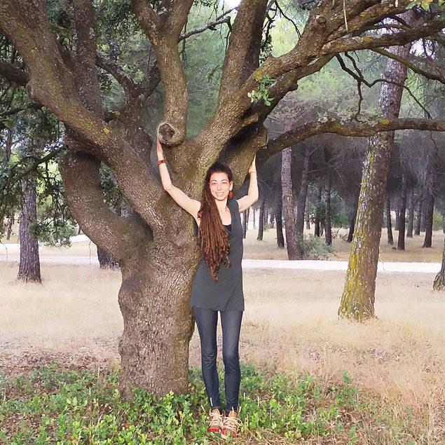 blanca martín de pie con los brazos en alto delante de un árbol, acompañamiento emocional con ecopsicología